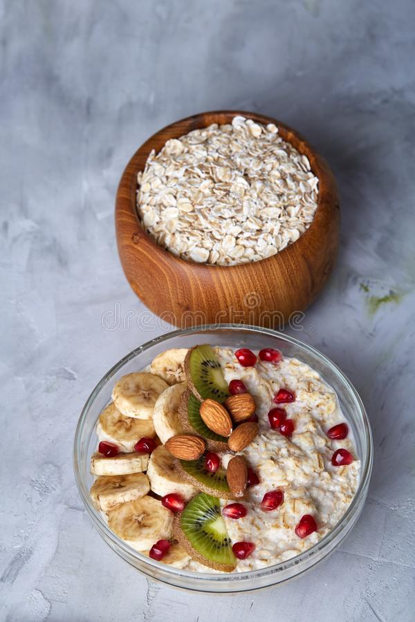 Diet breakfast oatmeal with fruits and bowl with oat flakes, selective focus, close-up, vertical stock photography