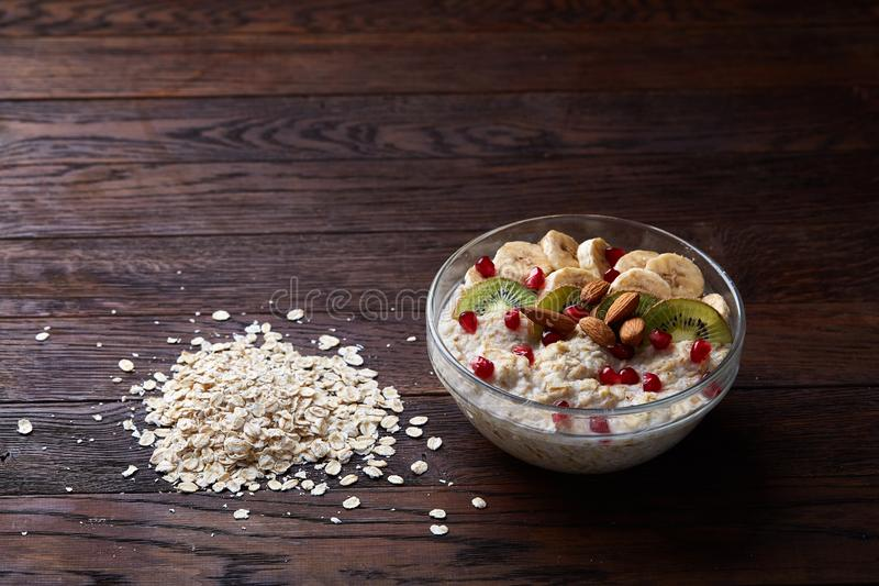 Diet breakfast oatmeal with fruits, bowl and spoon with oat flakes, selective focus, close-up royalty free stock photography