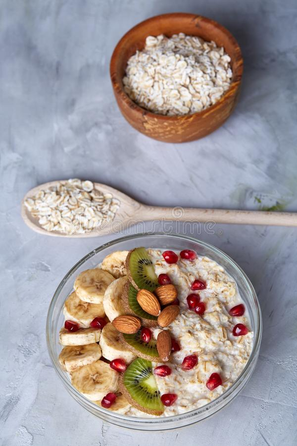 Diet breakfast oatmeal with fruits, bowl and spoon with oat flakes, selective focus, close-up royalty free stock image