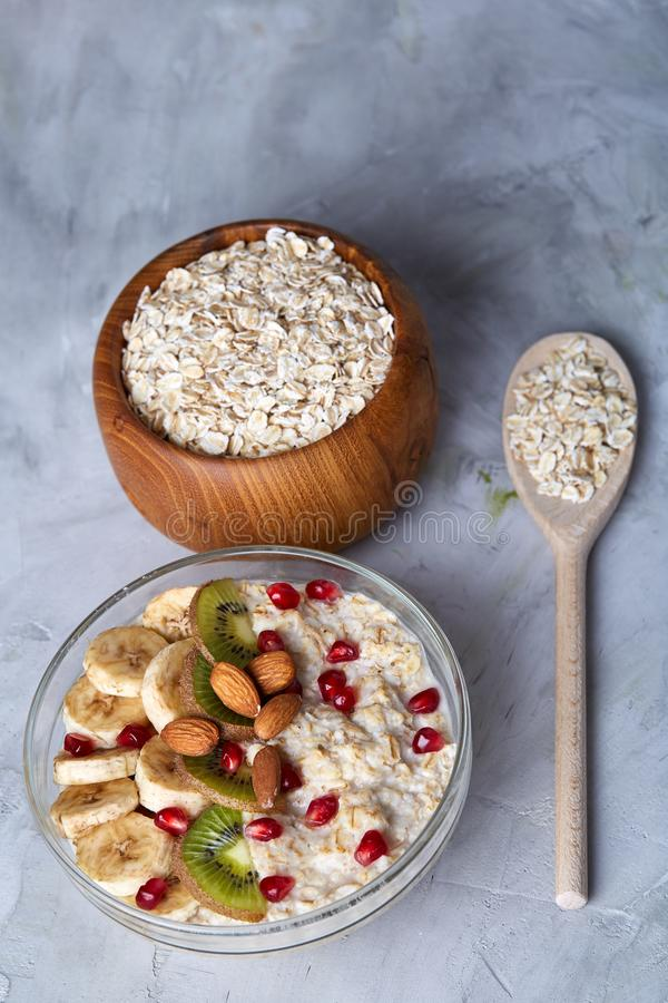Diet breakfast oatmeal with fruits, bowl and spoon with oat flakes, selective focus, close-up stock image