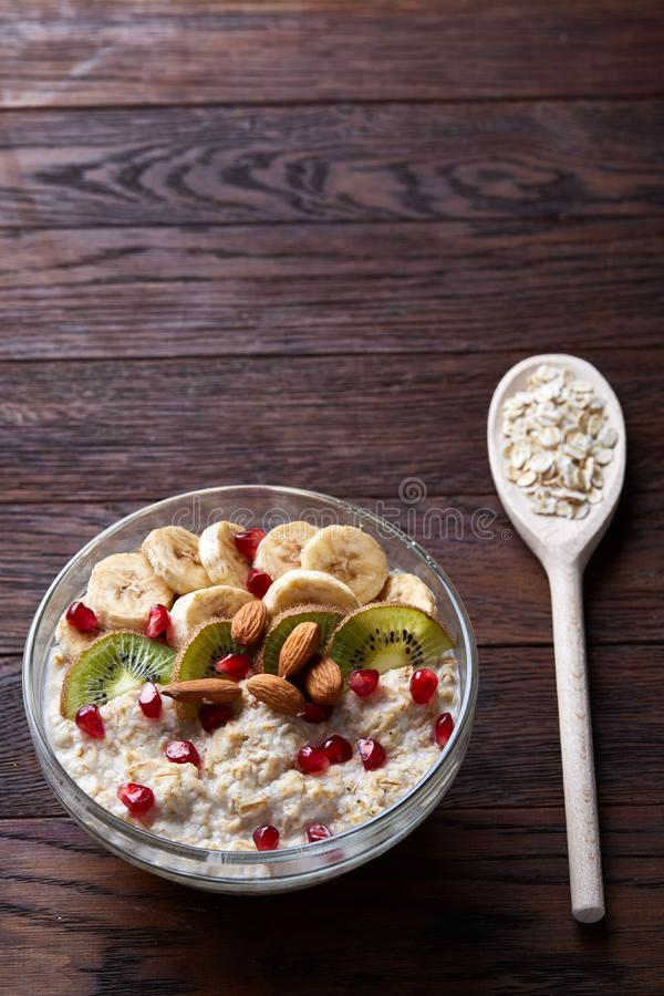 Diet breakfast oatmeal with fruits, bowl and spoon with oat flakes, selective focus, close-up royalty free stock photos