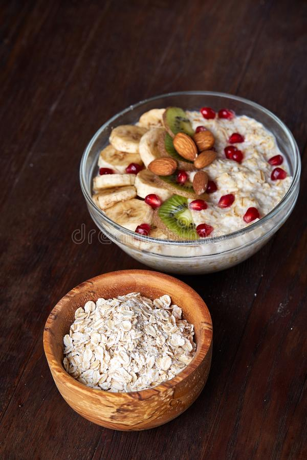 Diet breakfast oatmeal with fruits, bowl and spoon with oat flakes, selective focus, close-up royalty free stock images
