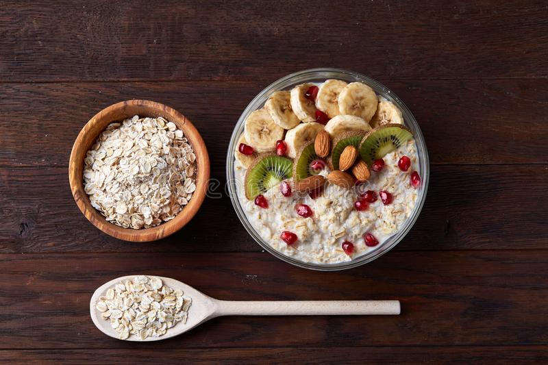 Diet breakfast oatmeal with fruits, bowl and spoon with oat flakes, selective focus, close-up stock photo