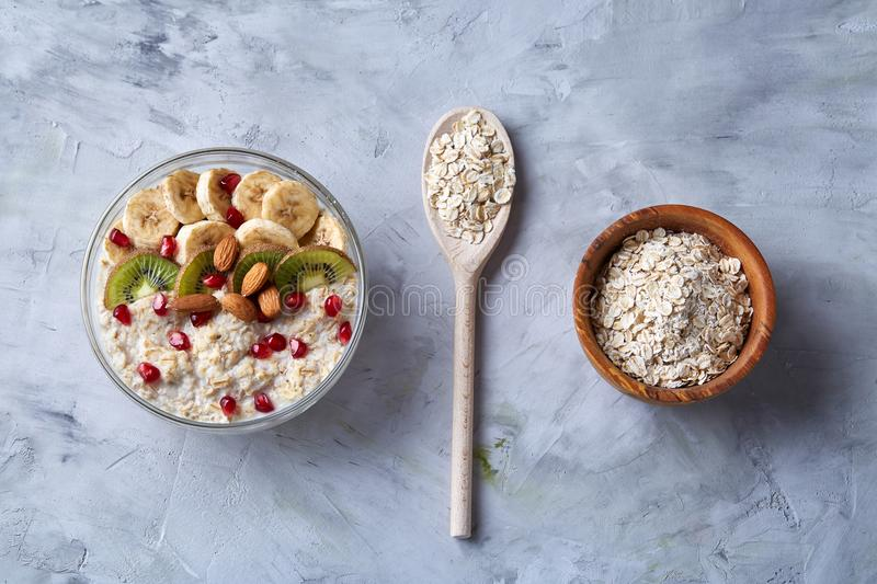 Diet breakfast oatmeal with fruits, bowl and spoon with oat flakes, selective focus, close-up stock photography