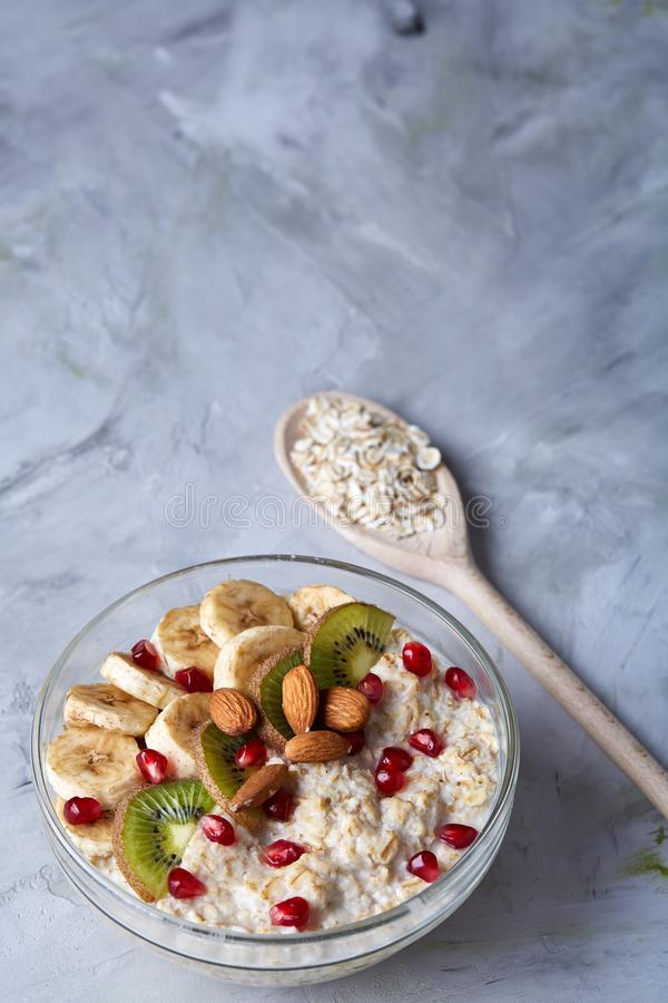 Diet breakfast oatmeal with fruits, bowl and spoon with oat flakes, selective focus, close-up stock photos