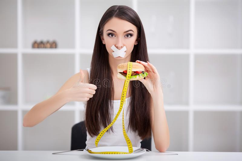 Diet. Close up face of young beautiful sad latin woman with mouth sealed on stick tape stock photo