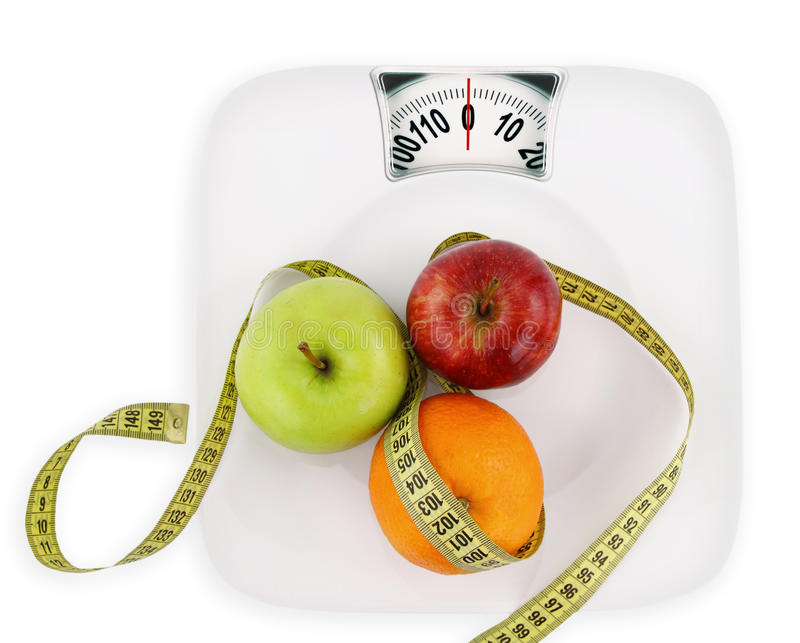 Diet concept. Fruits with measuring tape on a plate like weight scale royalty free stock images