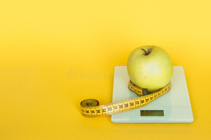 Diet concept. Apples and table top kitchen scales and measuring tape line on yellow background. royalty free stock photography