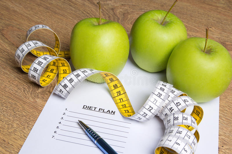 Diet concept - close up of paper with diet plan, apples and meas. Ure tape on wooden table stock photography
