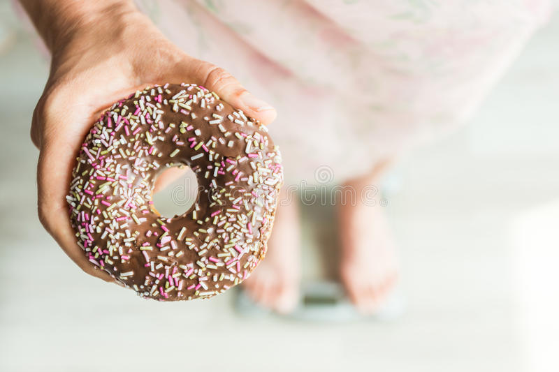 Diet Concept. Close-up of Woman`s feet On Weighing Scale With Donut. Concept of Sweets, Unhealthy Junk Food and obesity. royalty free stock image