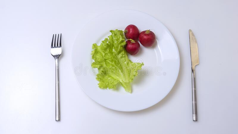 Diet concept. fresh vegetables on a white plate with fork and knife. stock photo