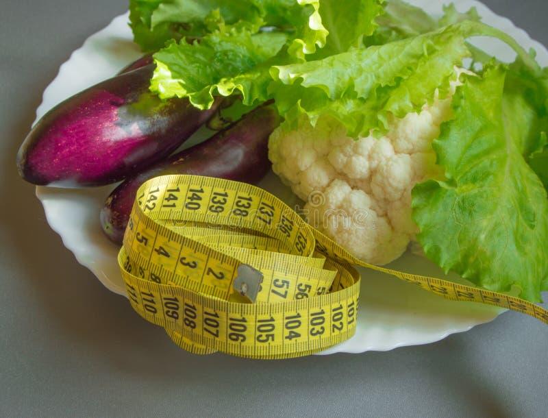 Diet concept, healthy eating, lettuce, cauliflower, eggplant, measuring tape vegetables stock photo