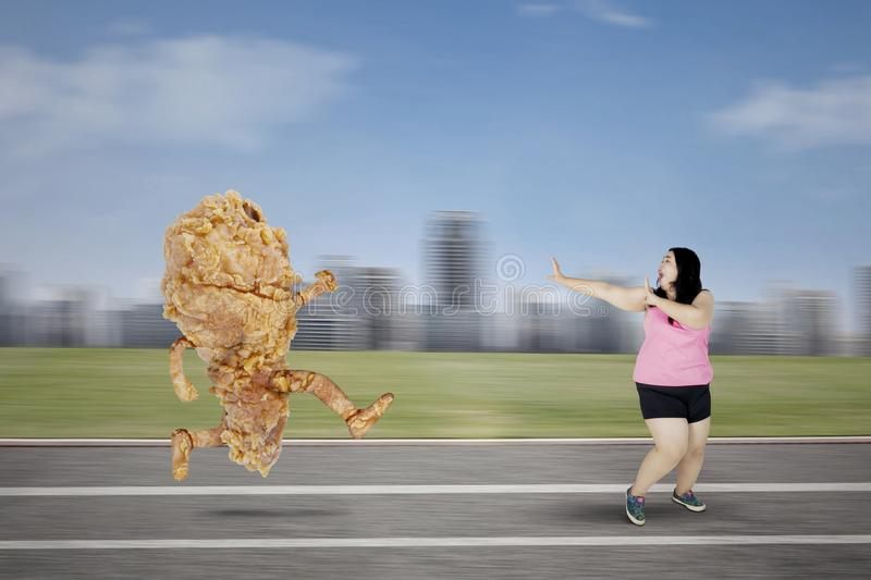 Obese woman escaping from a fried chicken. Diet concept. Obese woman escaping from a fried chicken while running on the track royalty free stock images