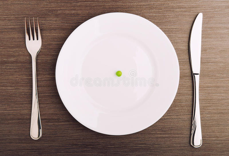 Diet concept. one pea on an empty white plate stock photo
