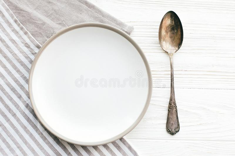 Diet concept. Stylish empty plate with vintage spoon on napkin on white table, flat lay. Modern set, serving for reception and. Party celebration. Copy space stock image