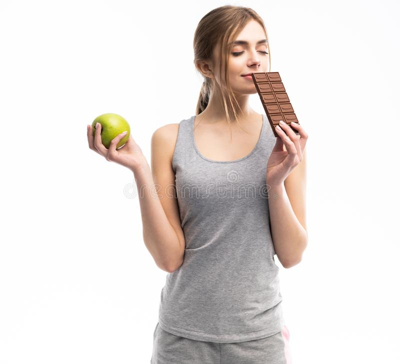 Diet. Dieting concept. Healthy Food. Beautiful Young Woman choosing between Healthy and Unhealthy Food.Fruits or Sweets royalty free stock photography