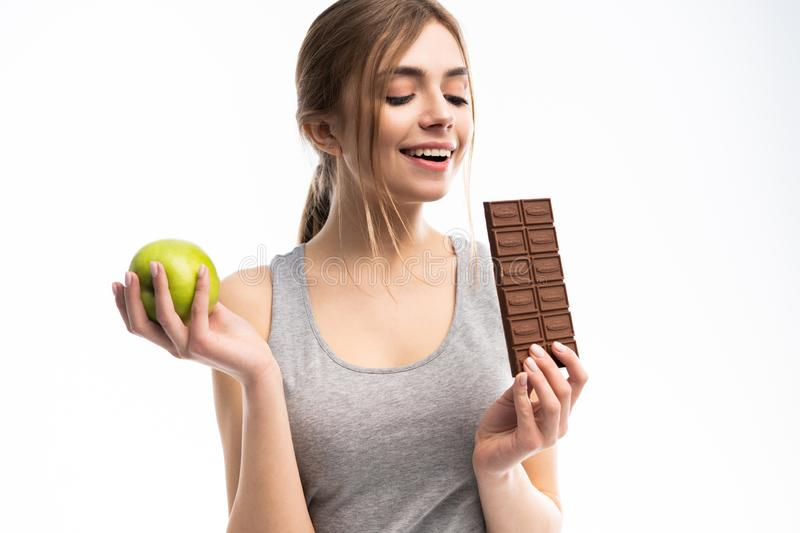 Diet. Dieting concept. Healthy Food. Beautiful Young Woman choosing between Healthy and Unhealthy Food.Fruits or Sweets royalty free stock photo