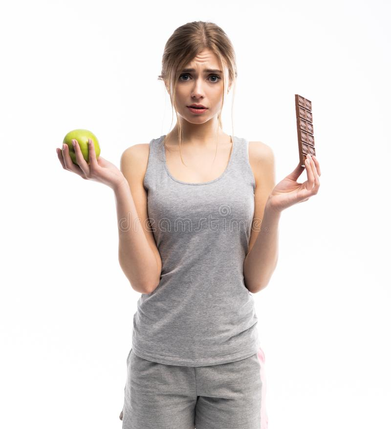 Diet. Dieting concept. Healthy Food. Beautiful Young Woman choosing between Healthy and Unhealthy Food.Fruits or Sweets stock photos