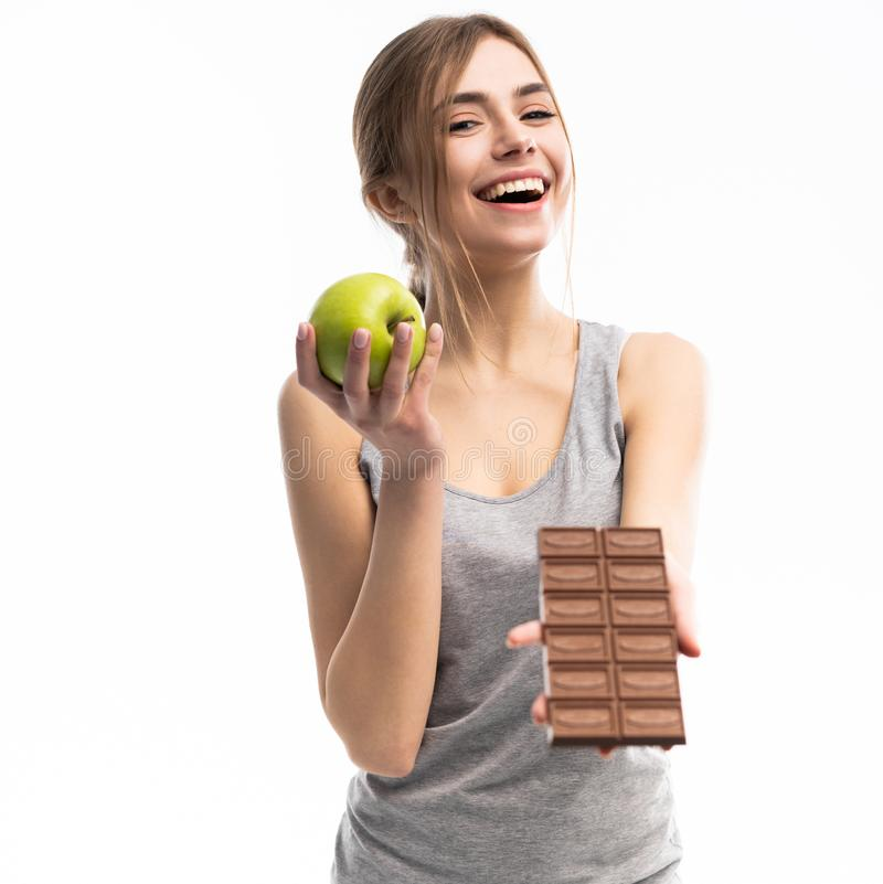 Diet. Dieting concept. Healthy Food. Beautiful Young Woman choosing between Healthy and Unhealthy Food.Fruits or Sweets royalty free stock photos