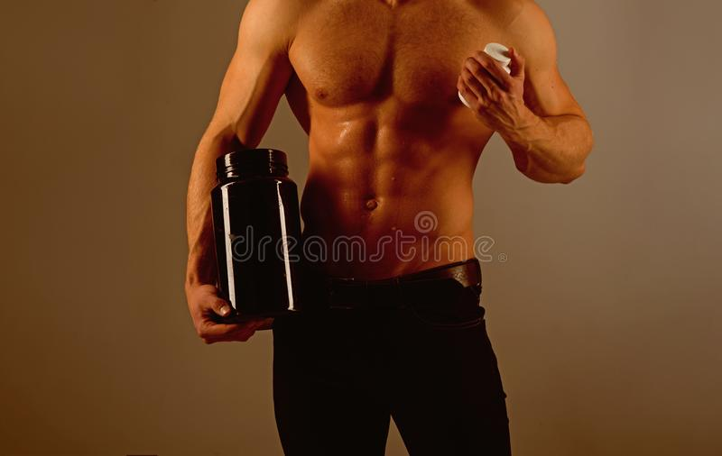 Diet effect. Strong man hold vitamin bottles. Healthy diet. Man with six pack abs. Stimulating muscle growth with. Anabolic steroids. Anabolic hormone increases stock photography