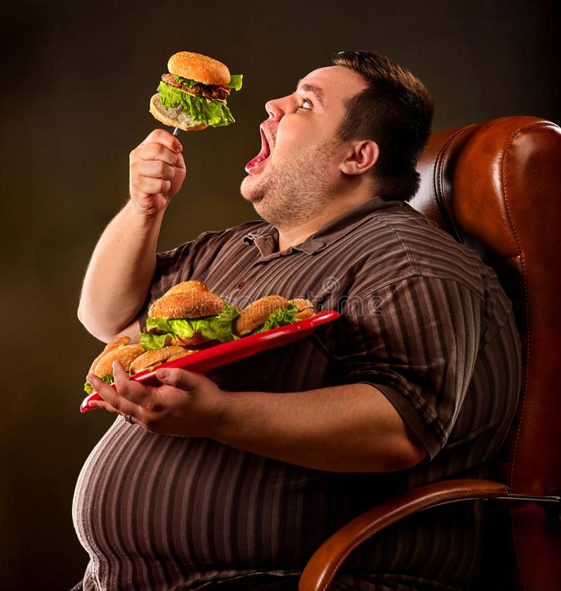 Fat man eating fast food hamberger. Breakfast for overweight person. Diet failure of fat man eating fast food hamberger. Happy overweight person with wide-open royalty free stock photo