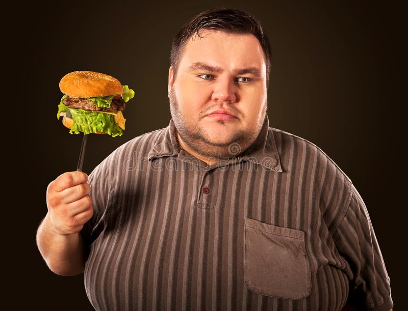 Fat man eating fast food hamberger. Breakfast for overweight person. Diet failure of fat man eating fast food hamberger. Happy overweight person with wide-open stock image
