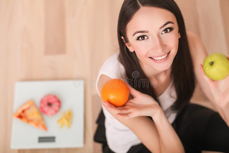 Diet And Fast Food Concept. Overweight Woman Standing On Weighing Scale Holding Pizza. Unhealthy Junk Food. Dieting, Lifestyle. We stock images