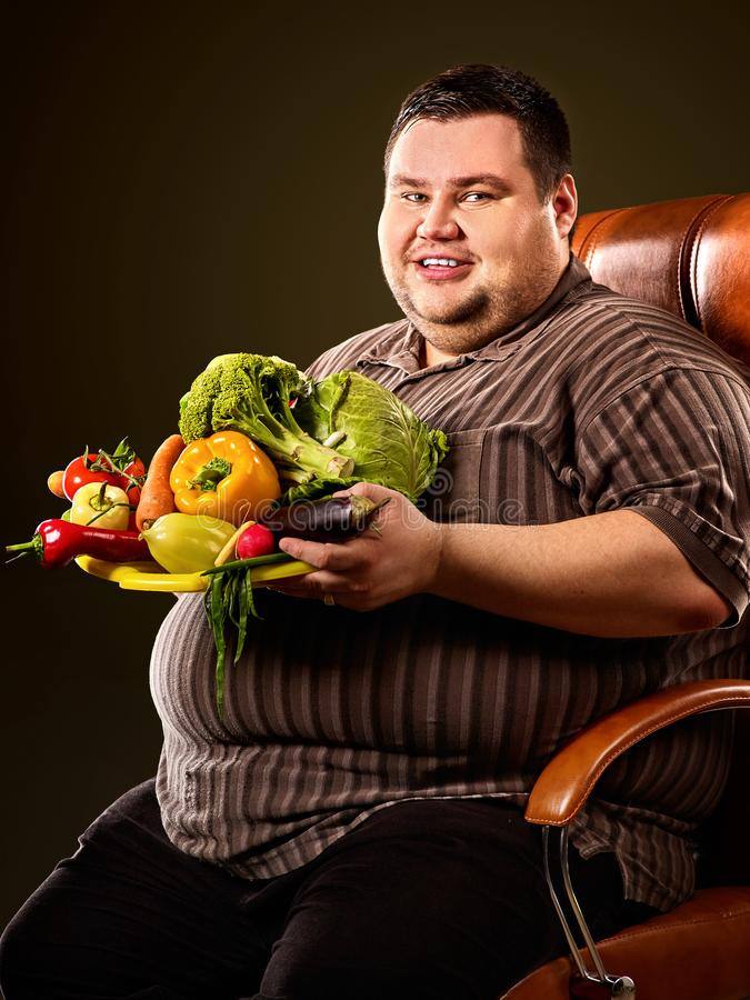 Diet fat man eating healthy food. Healthy breakfast with vegetables. Diet fat man eating healthy food with vegetables cauliflower and sweet pepper with radish royalty free stock photo