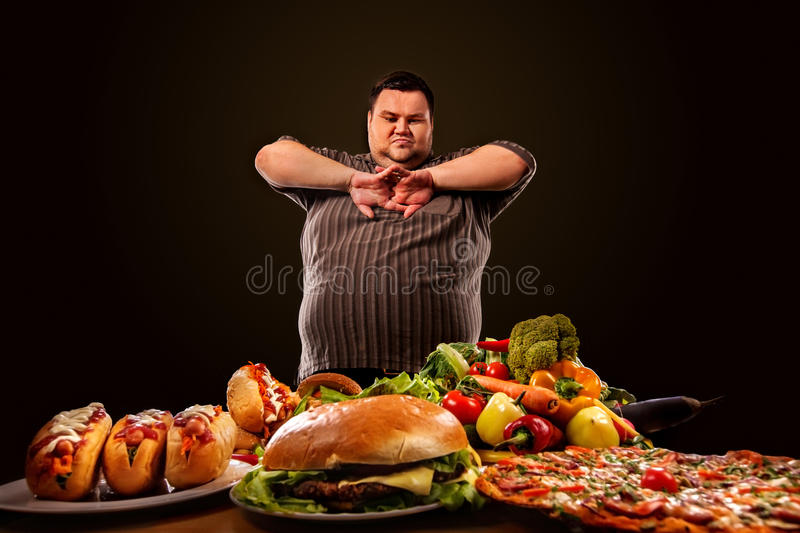 Diet fat man makes choice between healthy and unhealthy food. stock image