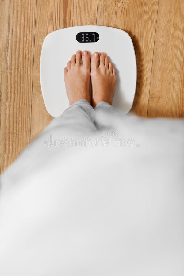 Diet. Female Feet On Weighing Scale. Weight Loss. Healthy Lifestyle. Diet. Top View Of Female Bare Feet Standing On A Scale. Caucasian Young Woman Measuring stock image