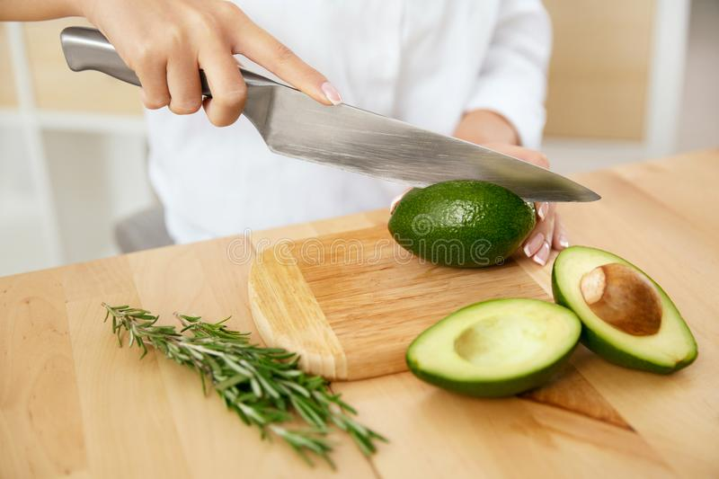 Diet. Female Hands Cutting Avocado In Kitchen. stock images
