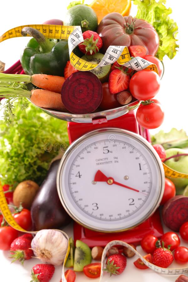 Diet food concept. Fruit and vegetable on balance royalty free stock photos