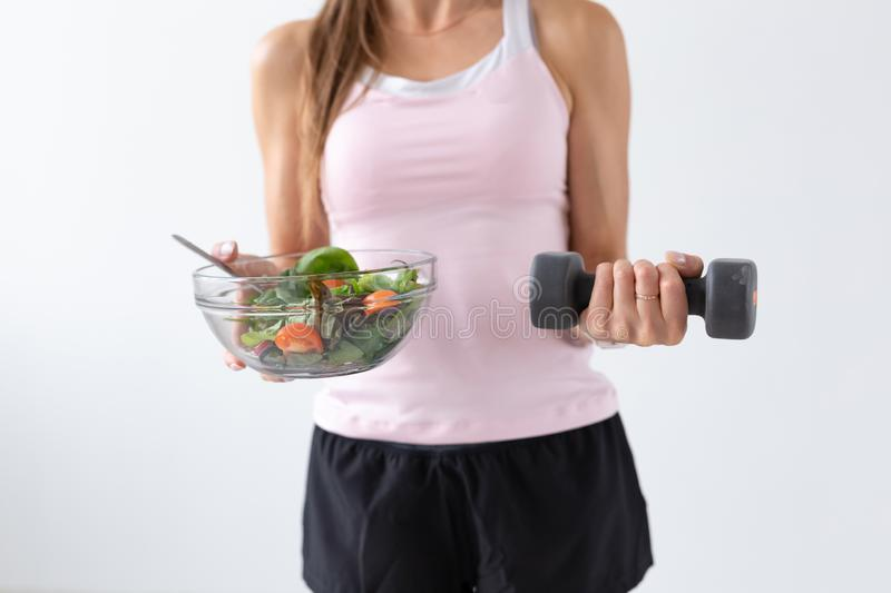 Diet, food and fitness concept - Close up of healthy salad and dumbbell in female hand over white background.  stock images