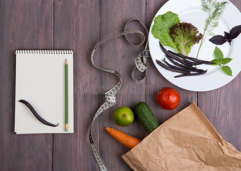 Diet Food Taary - Notebook zum Zählen von Kalorien, Zentimeter Klebeband, frisches Gemüse in Öko-Papiertasche und Teller mit Grün lizenzfreie stockfotografie