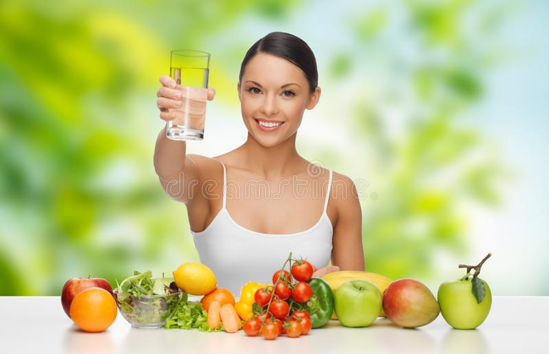 Woman with healthy food on table drinking water. Diet, healthy eating and people concept - woman with food on table drinking water over green natural background royalty free stock photos