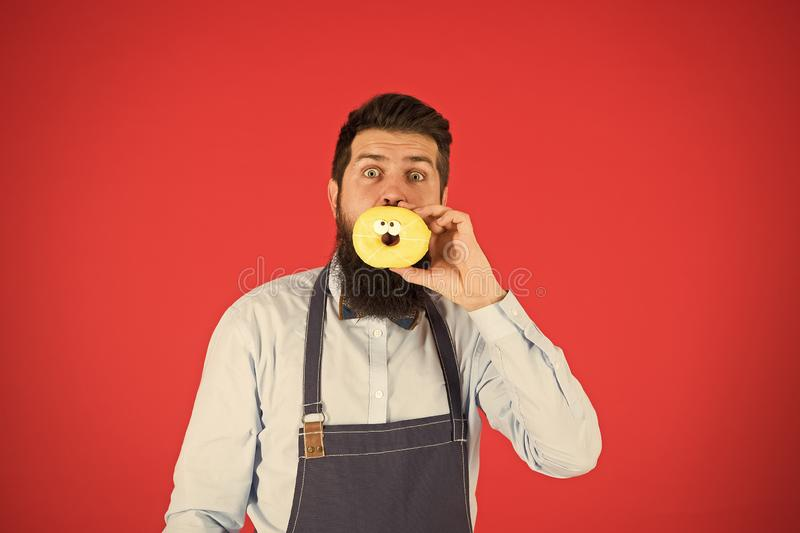 Diet and healthy food. Baker eat doughnut. Chef man in cafe. Calorie. Feel hunger. Bearded baker. Bearded man in apron royalty free stock image