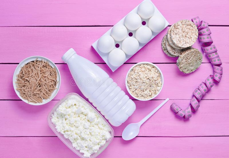 Diet, healthy food. Bottle of yogurt, crispy round bread, buckwheat noodles, oatmeal, cottage cheese, egg tray on a blue wooden b royalty free stock photo