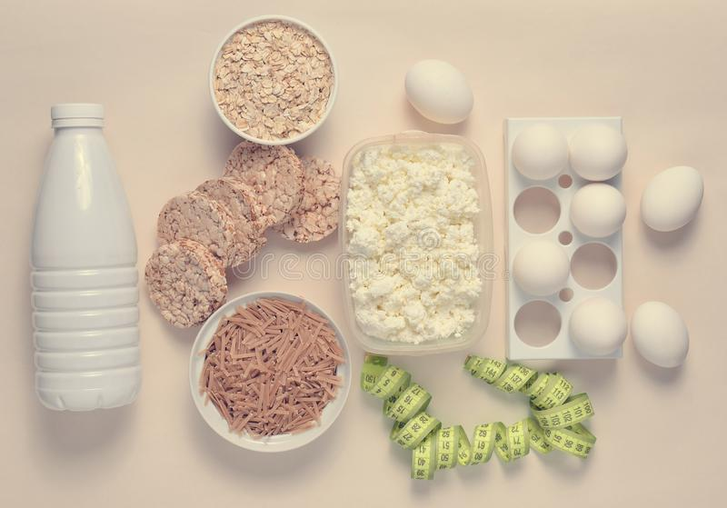Diet, healthy food. Bottle of yogurt, crispy round bread, buckwheat noodles, oatmeal, cottage cheese, egg tray, ruler on a white stock images