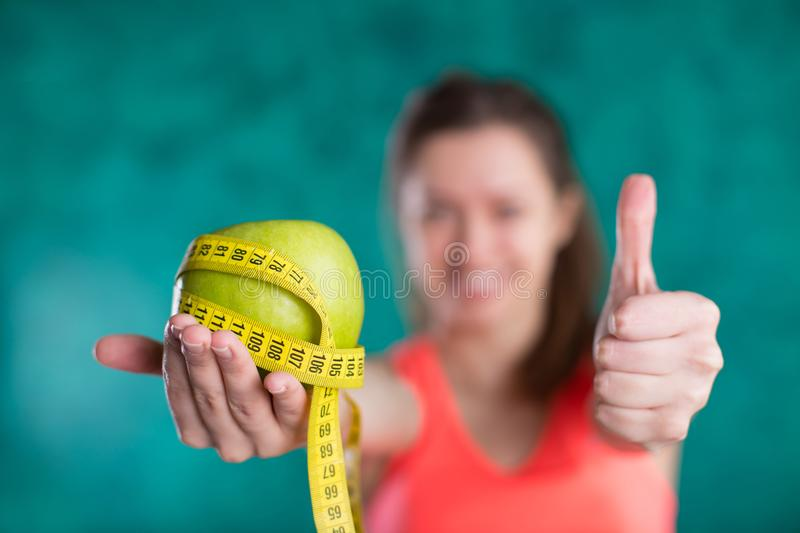 Diet. Healthy happy female with apple and tape measure for diet and weight loss concept - isolated on the turquoise background. royalty free stock photography