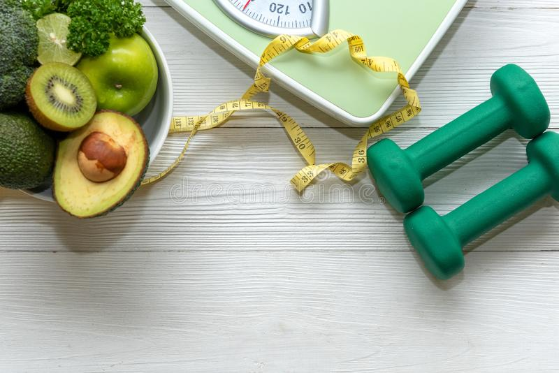 Diet and Healthy life loss weight Concept. Green apple and Weight scale measure tap with fresh vegetable and sport equipment for w. Omen diet slimming. Top view royalty free stock image