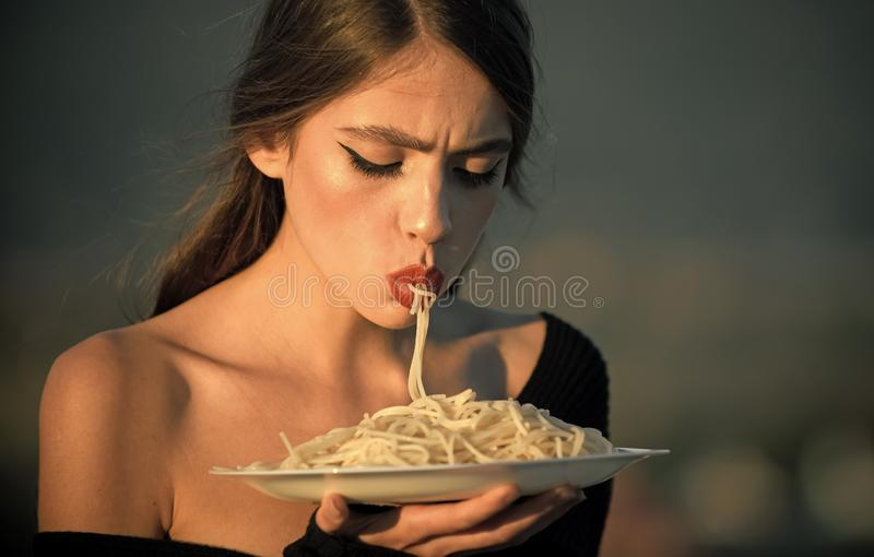 Diet and healthy organic food, italy. Chef woman with red lips eat pasta. Hunger, appetite, recipe. Woman eating pasta stock photography