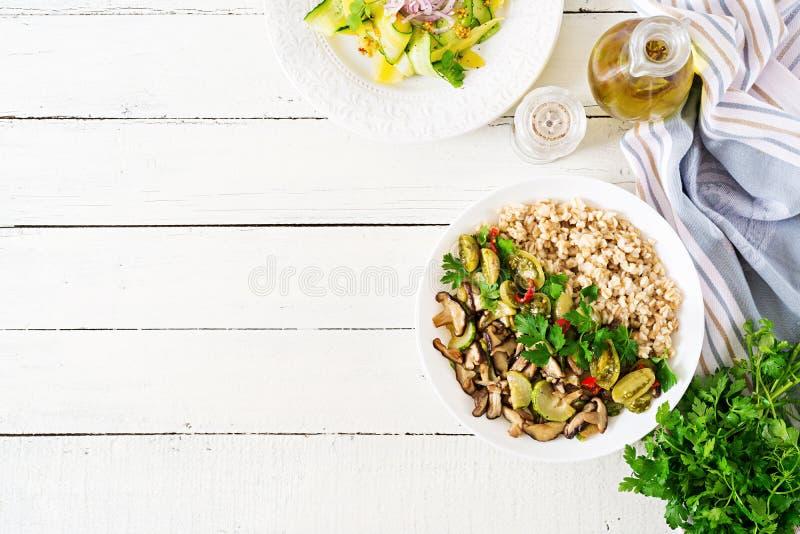 Diet menu. Healthy vegetarian meal - mushrooms shiitake, zucchini and oatmeal porridge on bowl. Vegan food. Flat lay. Top view royalty free stock image