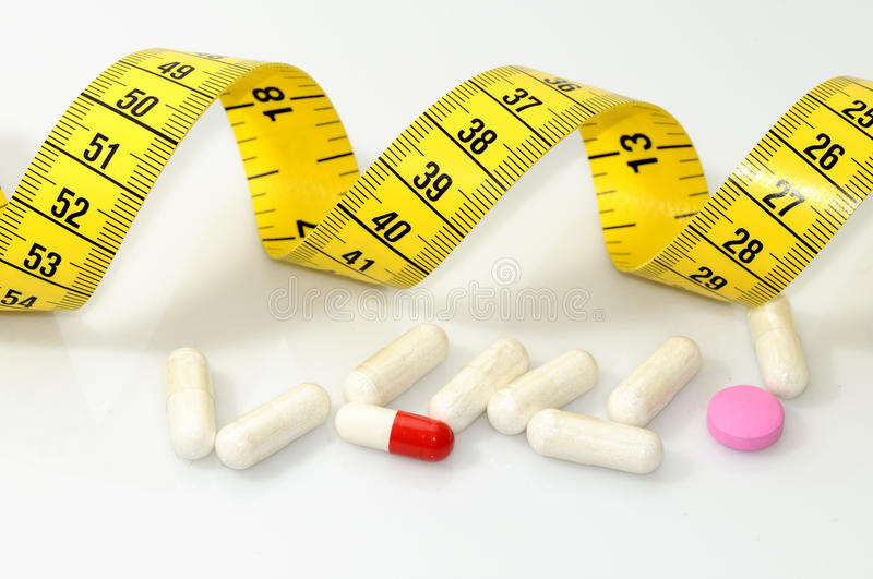 Diet pills. Tape measure and diet pills. white backgrounds royalty free stock photography