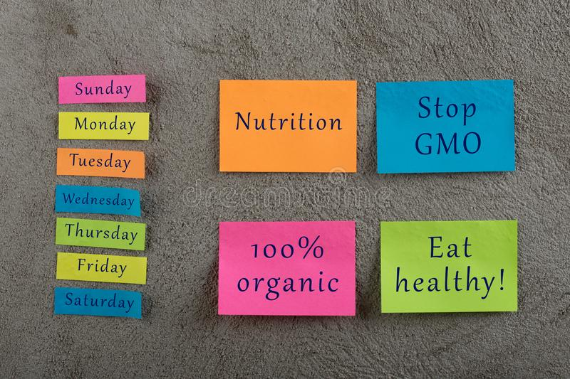 Diet plan concept - Many colorful sticky note with words nutrition, eat healthy, stop gmo, 100 percent organic and days of week. On grey cement background stock photo