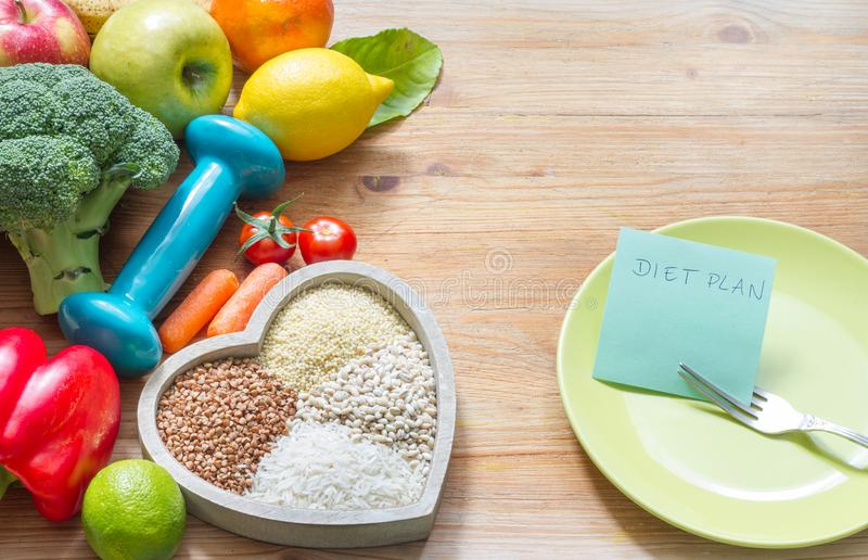 Diet plan and healthy lifestyle concept with vegetarian food in heart and gym dumbbell. Background stock photo