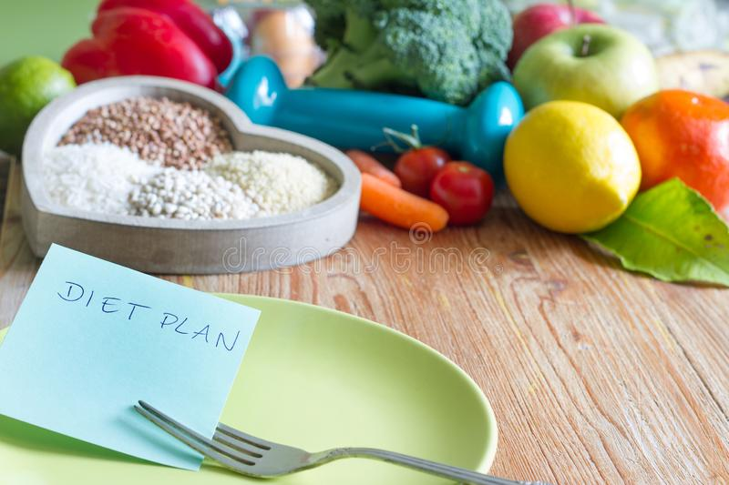 Diet plan and healthy lifestyle concept with vegetarian food in heart and gym dumbbell. Background stock images