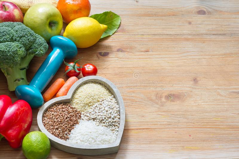 Diet plan and healthy lifestyle concept with vegetarian food in heart and gym dumbbell. Background stock photography