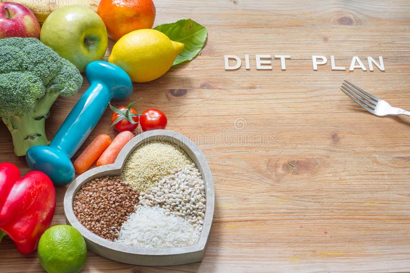 Diet plan and healthy lifestyle concept with vegetarian food in heart and gym dumbbell. Background stock image
