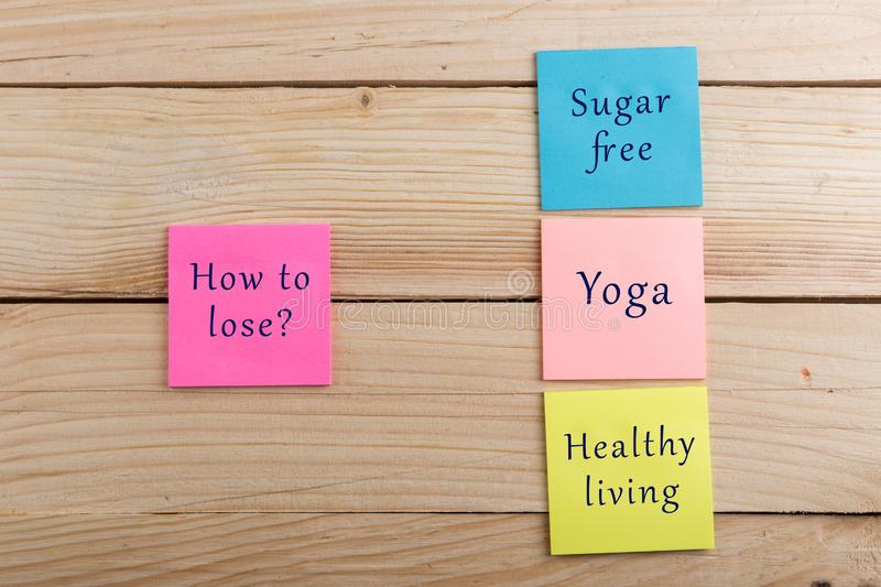 Diet plan and motivation concept - Many colorful sticky note with words how to lose, sugar free, yoga, healthy living. On grey cement background, sticker royalty free stock photography