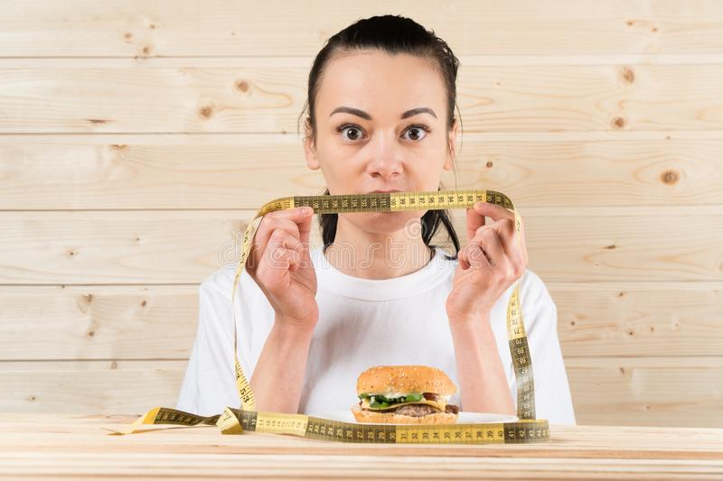 Diet. Portrait woman wants to eat a Burger but stuck skochem mouth, the concept of diet, junk food, willpower in nutrition royalty free stock images